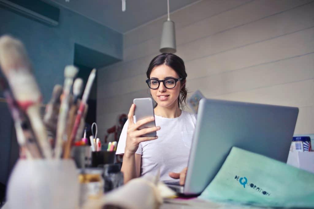 Foto de um mulher de óculos de grau, segurando um celular, na frente de um notebook, com canetas e papeis na mesa ao seu redor.