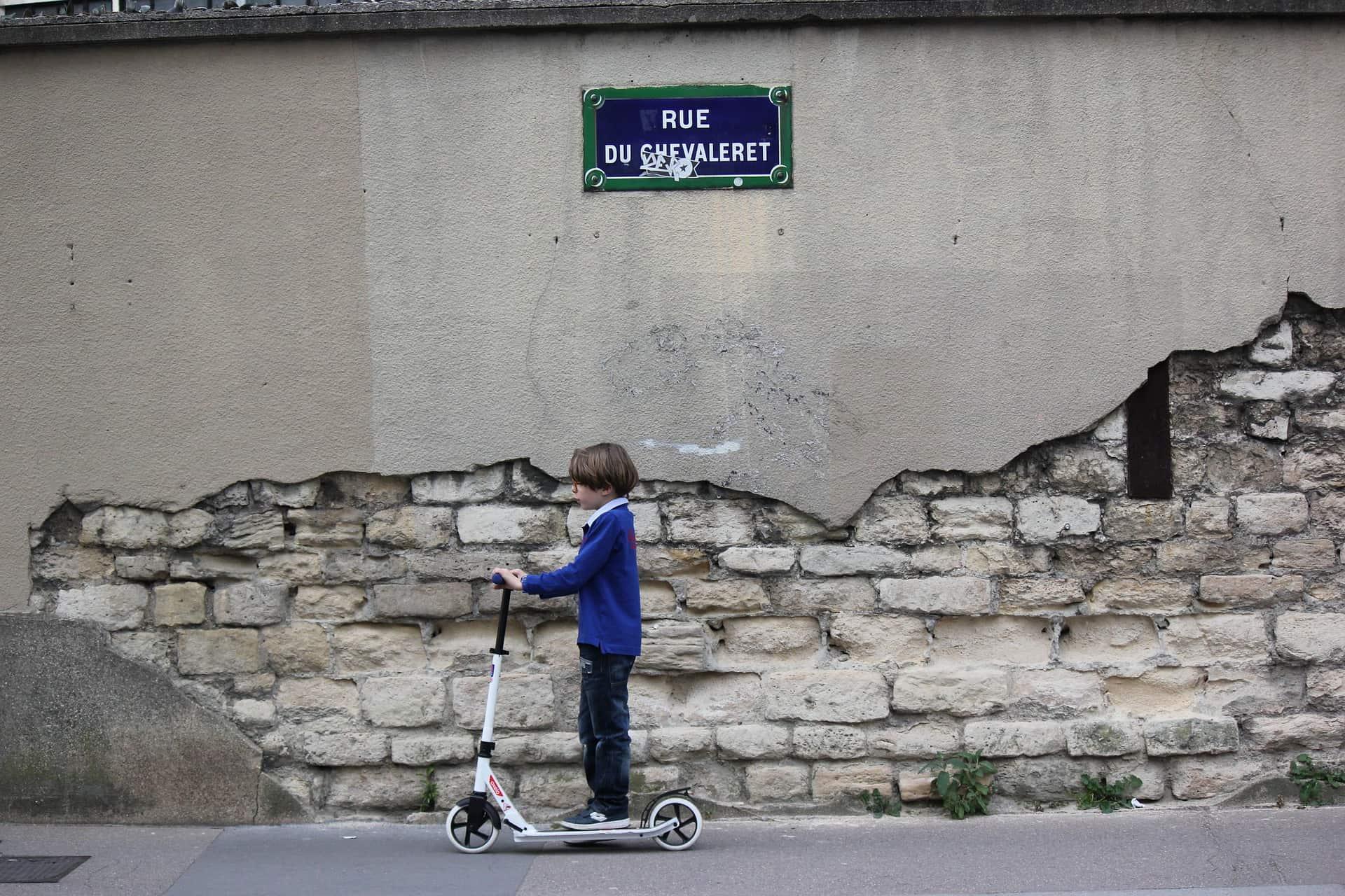 Menino anda de patinete na calçada com um muro rústico ao fundo.