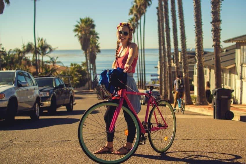 Mulher em pé, sorrindo com uma bicicleta rosa ao lado. Ao fundo, há palmeiras e um mar.