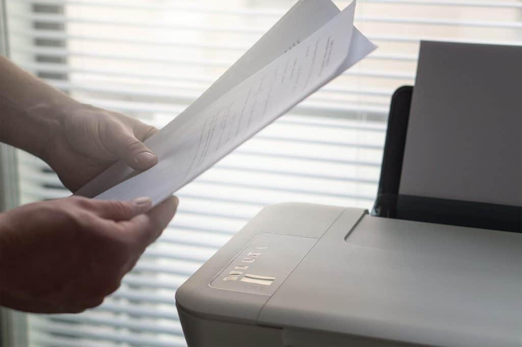 Imagem mostra mãos de uma pessoa segurando papéis ao lado de uma impressora.