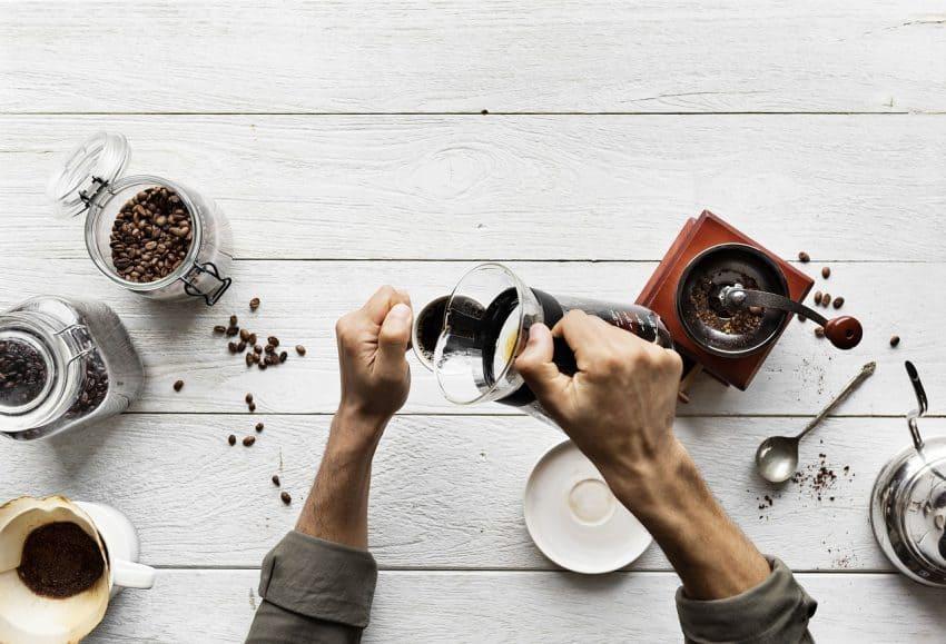 Pessoa servindo café com moedor e grãos ao redor.