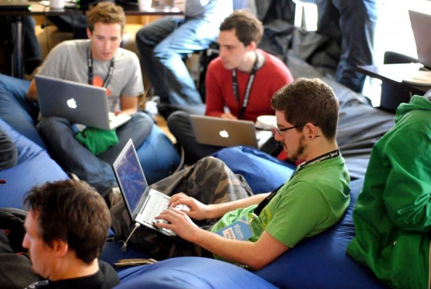 Imagem de pessoas sentadas em puffs azuis utilizando notebooks.