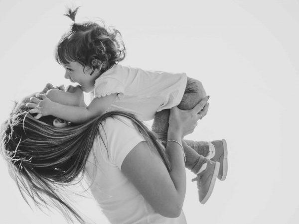 Na foto uma mulher com um bebê no colo sorrindo.
