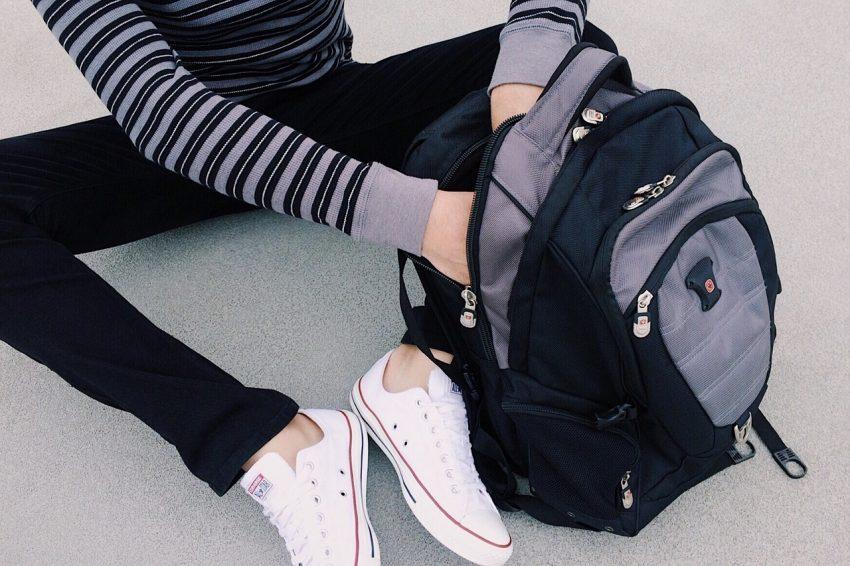Menina sentada procurando algo na mochila.