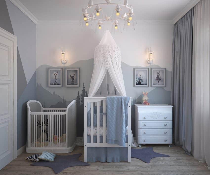 Quarto de bebê azul e branco, com parede decorada com pintura e quadros com berço branco com kit berço e mosquiteiro, cômoda e cercadinho para criança.