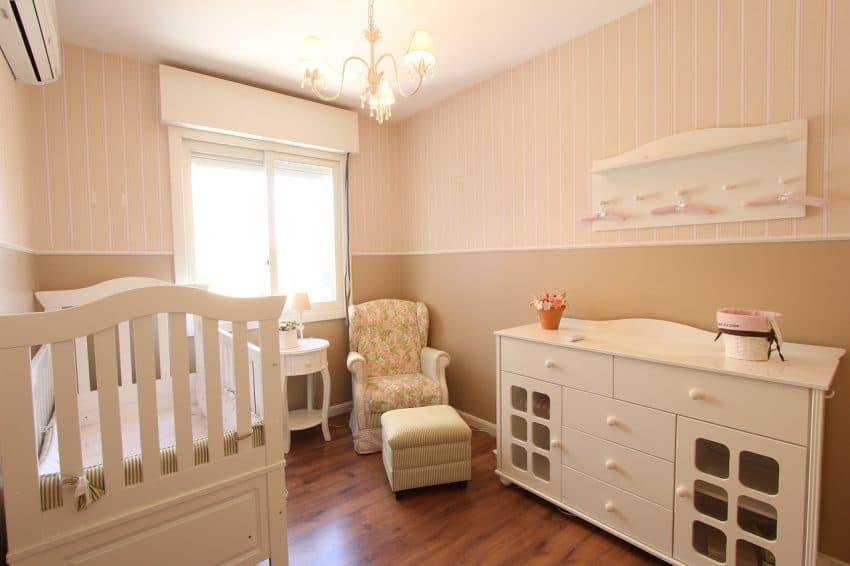 Quarto de bebê em tons pastéis, com berço decorado com kit berço simples, cômoda, poltrona e lustre.