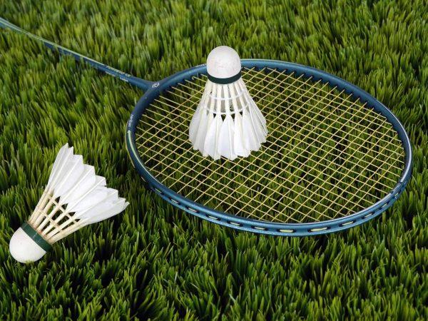 Uma raquete de badminton sobre a grama com uma peteca sobre a raquete e outra ao lado.