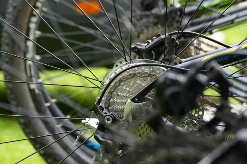 Detalhe de uma bicicleta destacando aro, câmbio e o material de produção.
