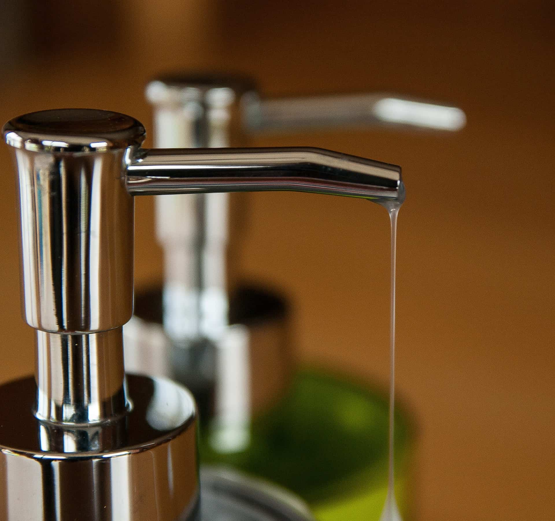 Imagem de sabonete íntimo em dispenser cromado com reflexo em espelho.