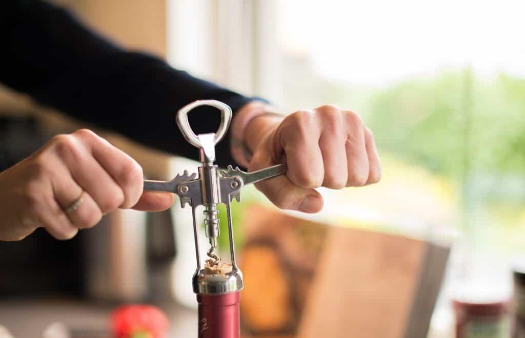 Na foto um homem abrindo uma garrafa de vinho com saca-rolhas.