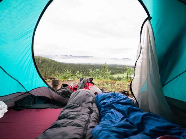Sacos de dormir cinza e azul dentro de barraca