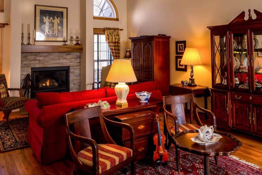 Imagem mostra duas luminárias acesas em meio a uma sala de estar bastante decorada. Uma, mais ao centro, acima de uma pequena cômoda de madeira, a outra, mais ao canto direito, sob uma pequena escrivaninha de madeira.