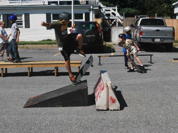 Criança com capacete andando de skate em uma pista.