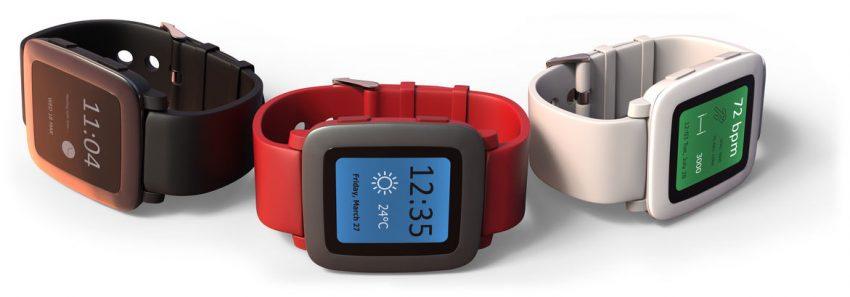 Três smartwatches com pulseiras coloridas.