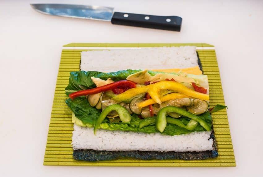 Faca santoku e sushi sendo preparado.
