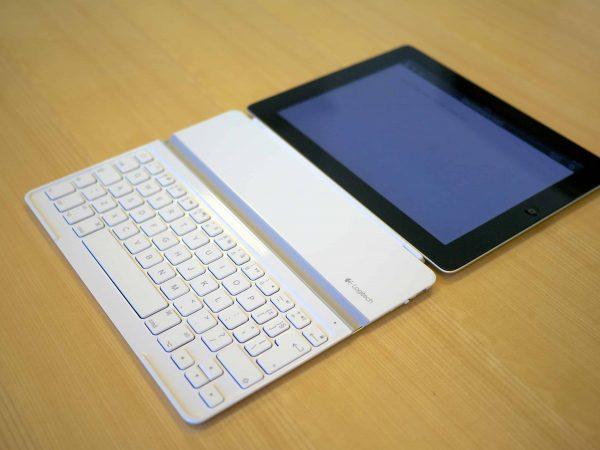 Imagem mostra um tablet com teclado em cima de uma mesa de madeira.