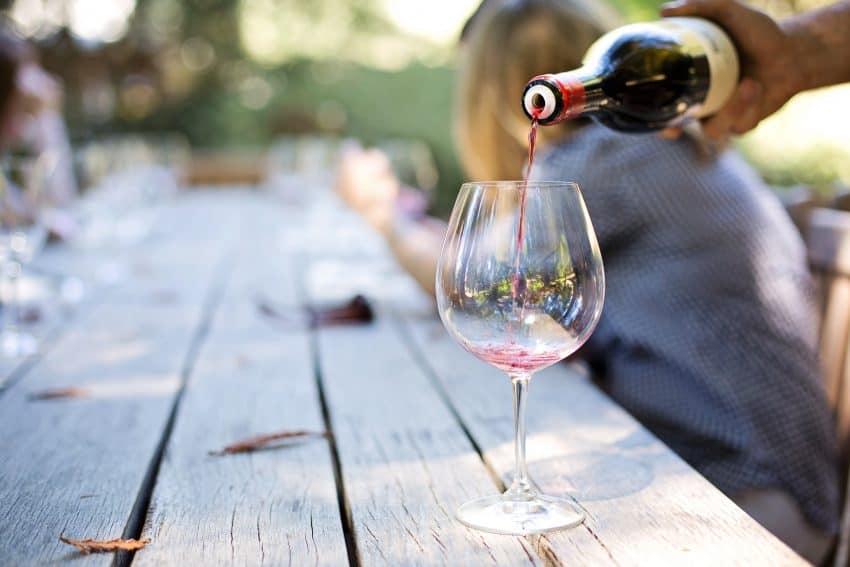 Foto a qual aparece a mão de uma pessoa segundo uma garrafa de vinho, e despejando o líquido dentro de uma taça, que está em cima de uma mesa de madeira.
