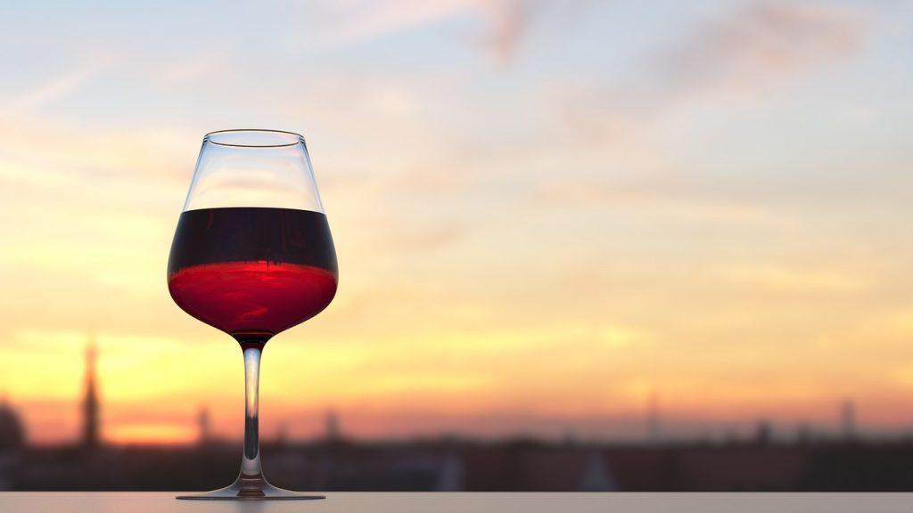 Na foto uma taça de vinho com o pôr do sol ao fundo.