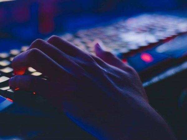 Imagem mostra uma mão em cima de um teclado mecânico gamer iluminado