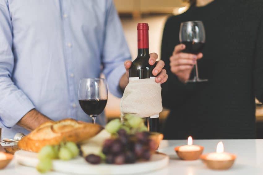 Foto que mostra do ombro ao quadril de duas pessoas bebendo vinho, sendo que uma delas segura a garrafa que está em cima de uma bancada. Pão, uvas e velas também estão na bancada.