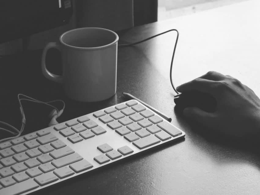 Imagem mostra a mão de uma pessoa sobre o mouse e um mini teclado ao lado.