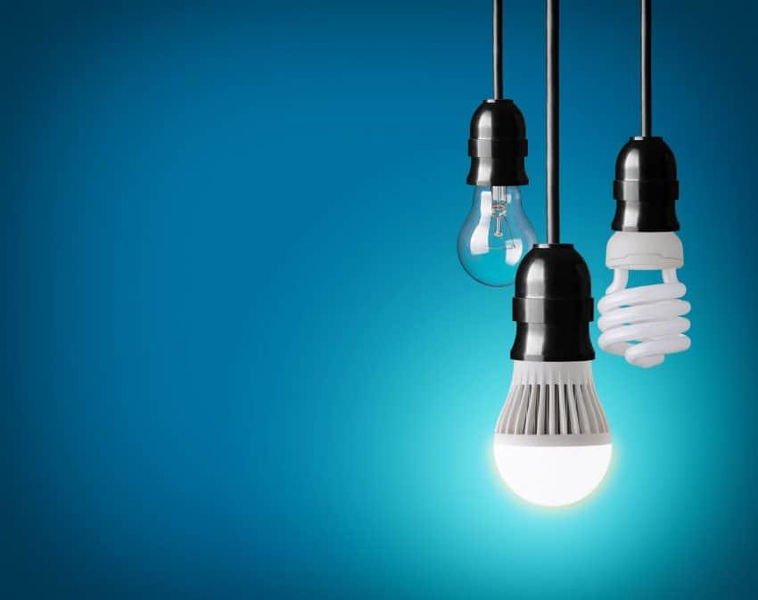 Três lâmpadas penduradas com fundo azul, uma delas está acesa.