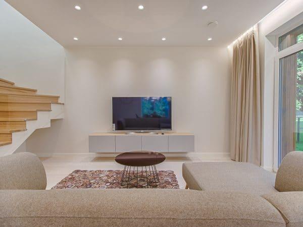Imagem mostra uma televisão de 55 polegadas em cima do rack de uma sala ampla.