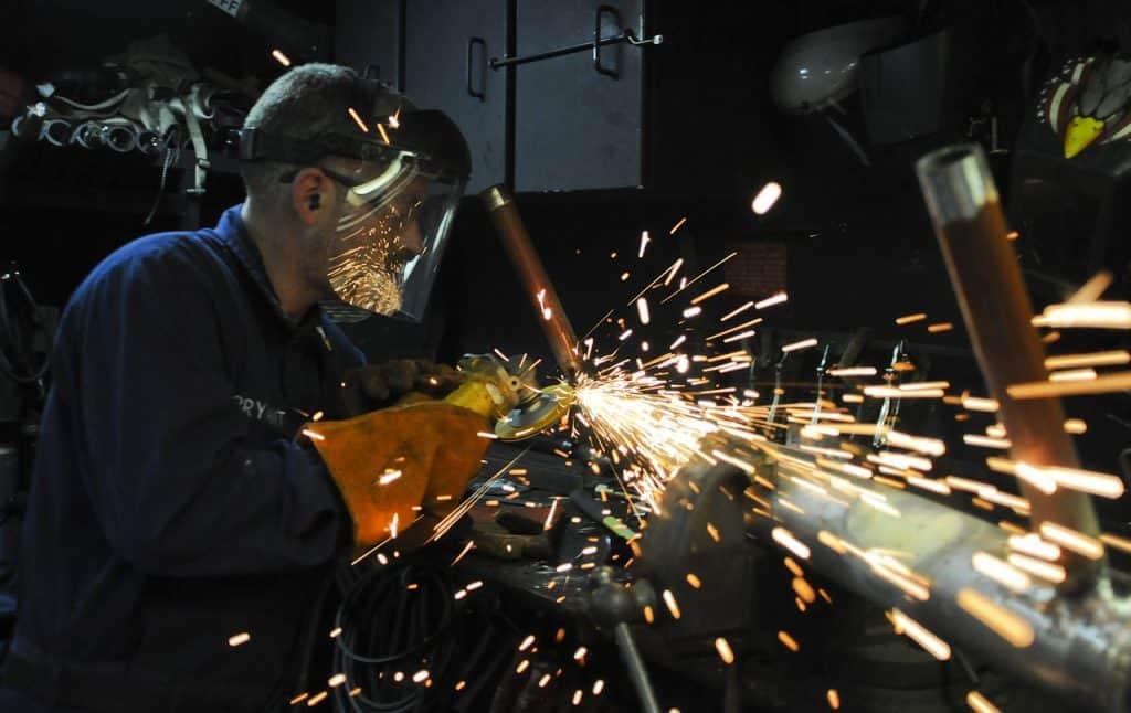 Um homem em uma oficina trabalhando com uma esmerilhadeira gerando faíscas de fogo