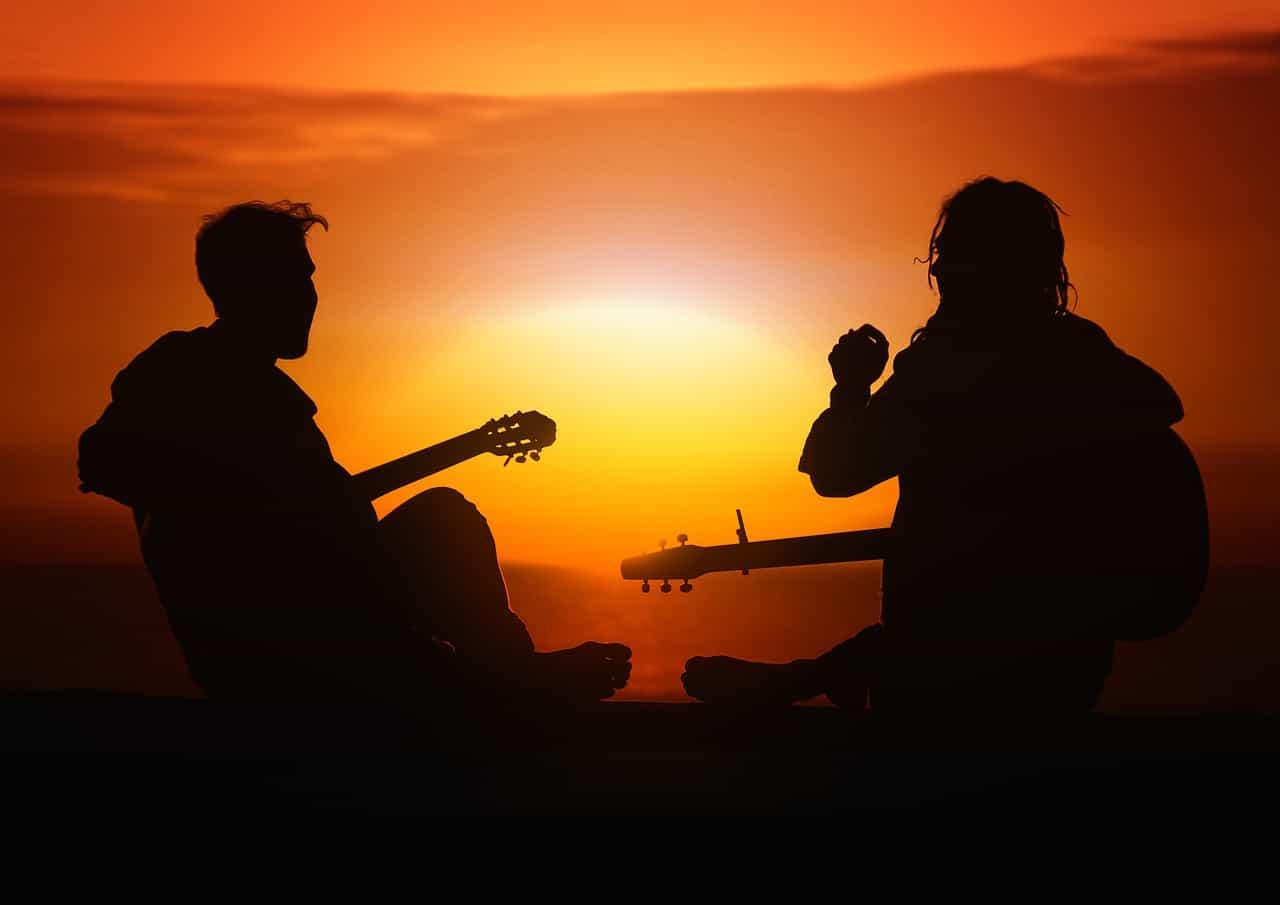 Silhueta de duas pessoas tocando violão no pôr do sol.