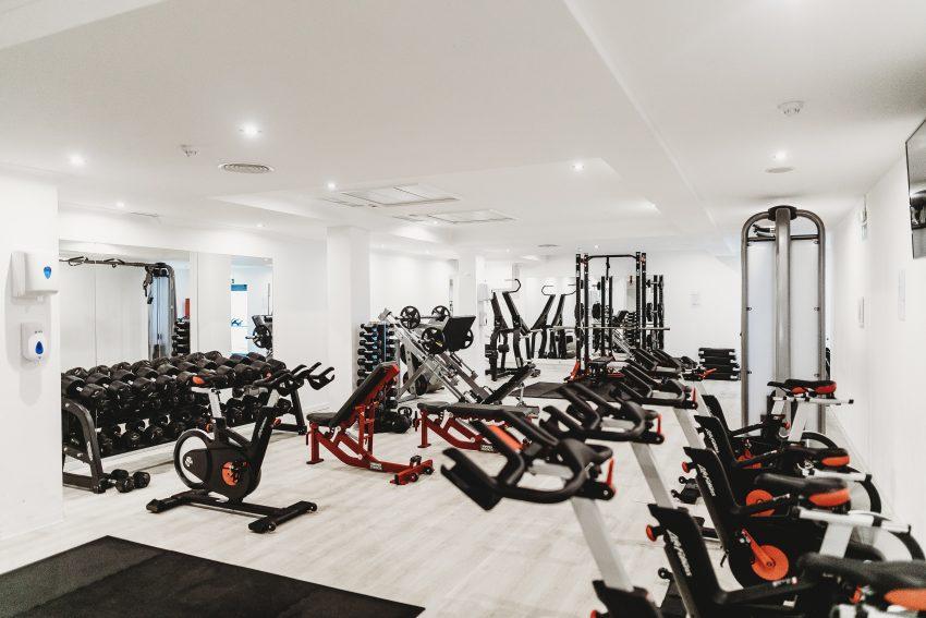 Imagem mostra diversas bicicletas de spinning dentro de uma academia.