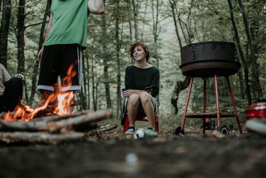 Pessoas em um acampamento na mata com fogueira acesa.