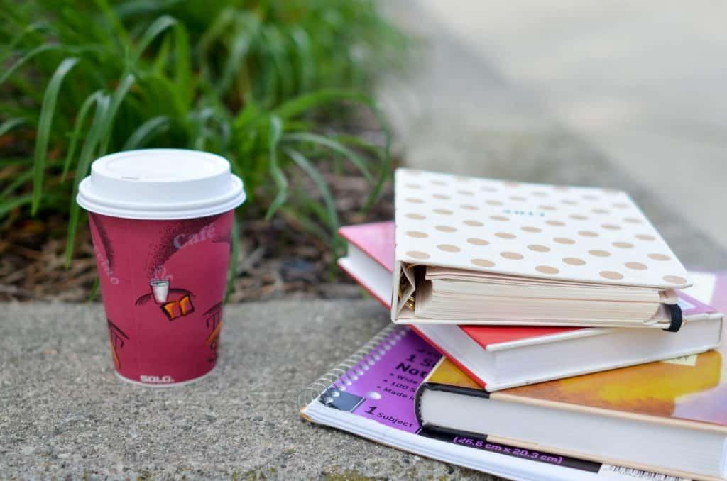 Imagem de agendas e livros com café ao lado.