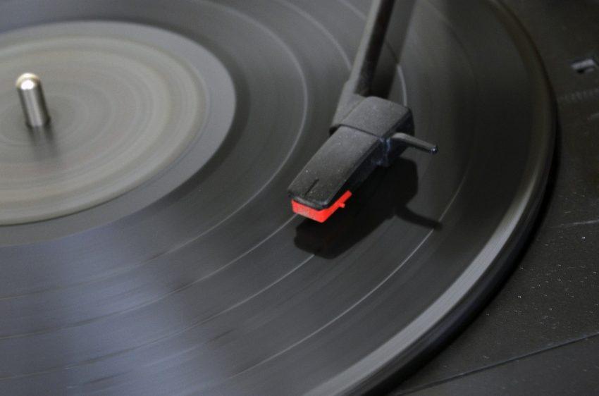 Imagem de vitrola manual durante a reprodução de um disco.