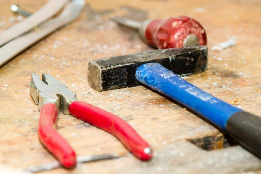 Imagem mostra em primeiro plano um alicate ao lado de um martelo, repousando sobre uma madeira gasta. Ao fundo, outras ferramentas desfocadas descansam na mesma madeira.