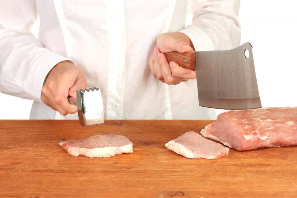 chef de cozinha usando amaciador de carne