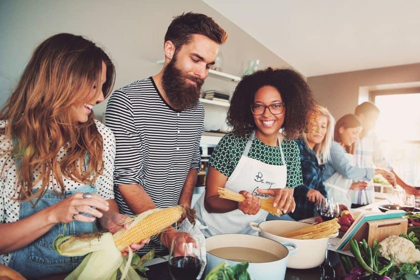 Grupo de amigos cozinhando juntos.