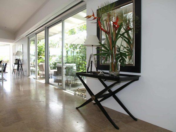 Sala espaçosa com um aparador de madeira. Em cima dele, há um abajur, um espelho e um vaso com flores grandes e altas.