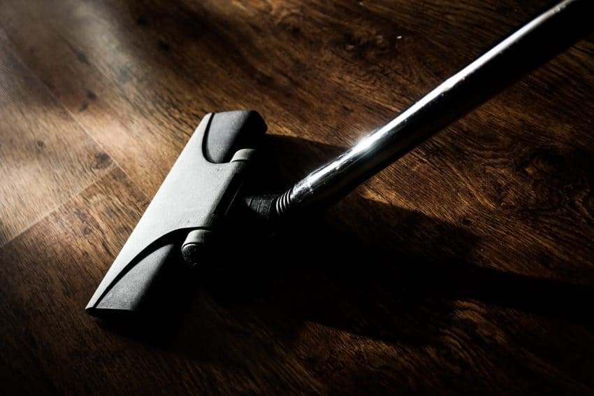 Aspirador sendo passado no chão de madeira.