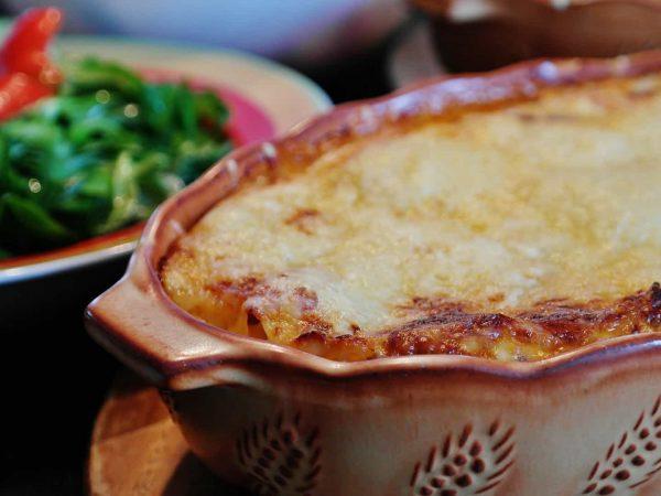 Imagem de uma lasanha em uma assadeira de cerâmica, com um prato de salada ao fundo.