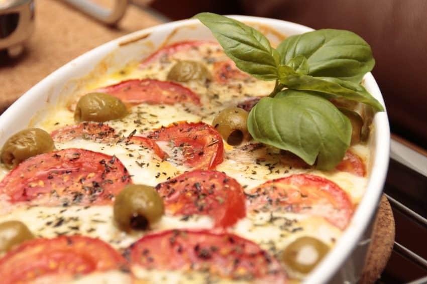 Imagem de uma receita com azeitonas, tomate, manjericão e queijo em uma assadeira de cerâmica branca.