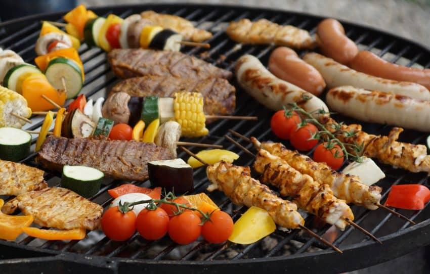 Na imagem, vemos diferentes tipos de alimentos sendo preparados na grelha de uma churrasqueira.