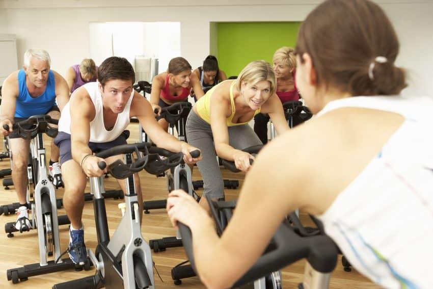 Imagem mostra uma aula de spinning na academia com várias pessoas.
