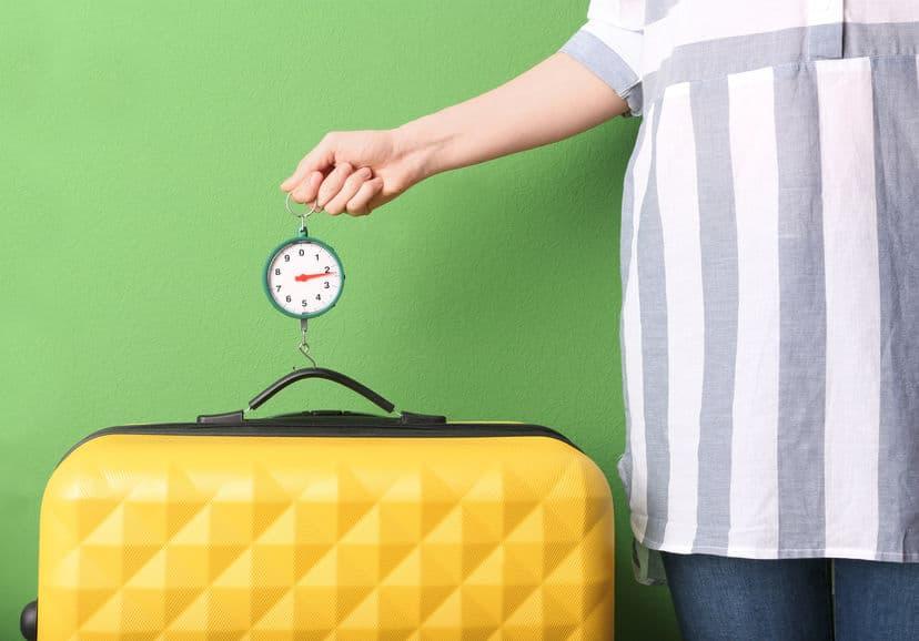 mão de uma mulher medida mala amarela com balança portátil