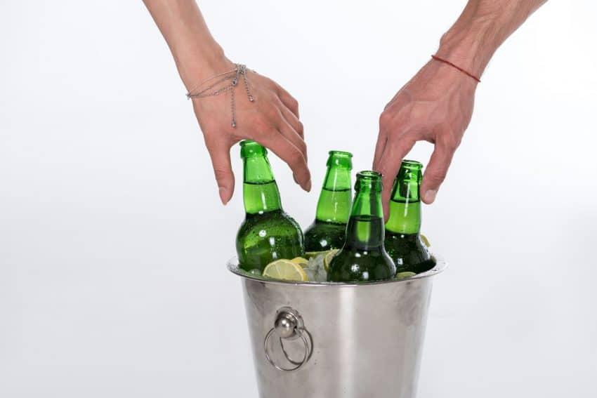 Close de duas mãos retirando cerveja de um balde de gelo.