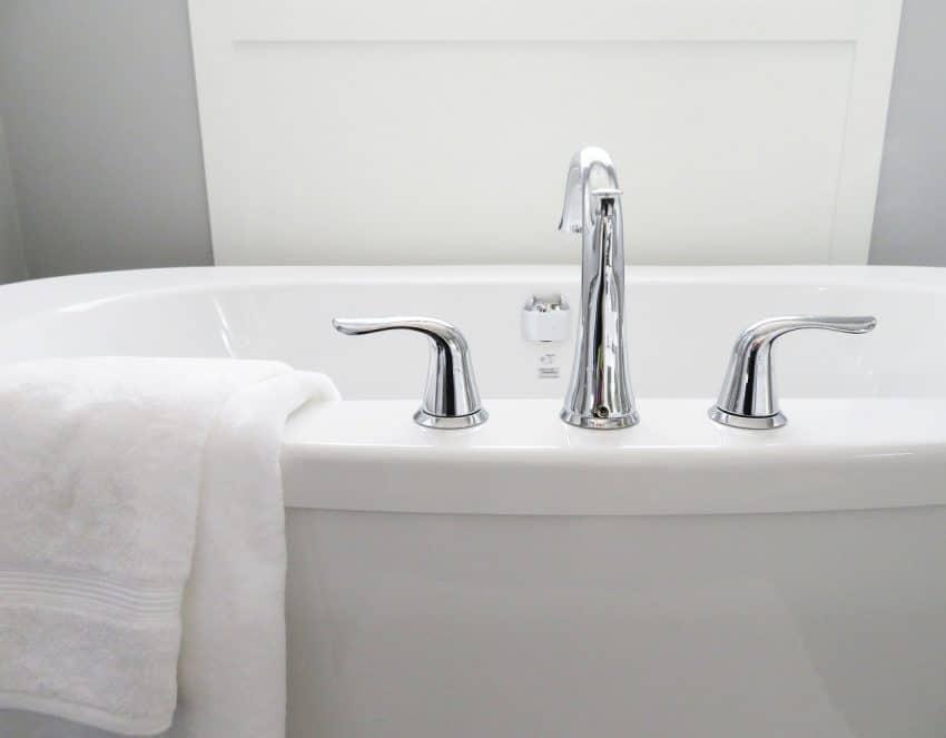 Imagem de uma banheira com uma toalha branca pendurada.