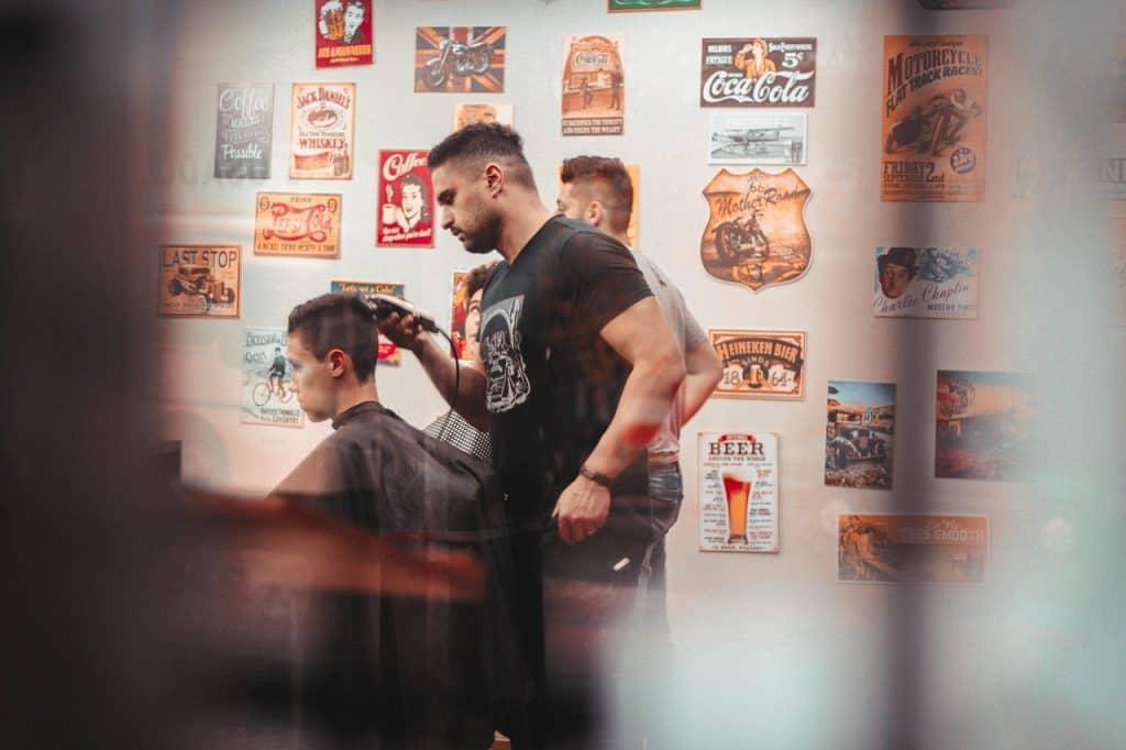 A imagem mostra um barbeiro fazendo um corte de cabelo em uma pessoa.