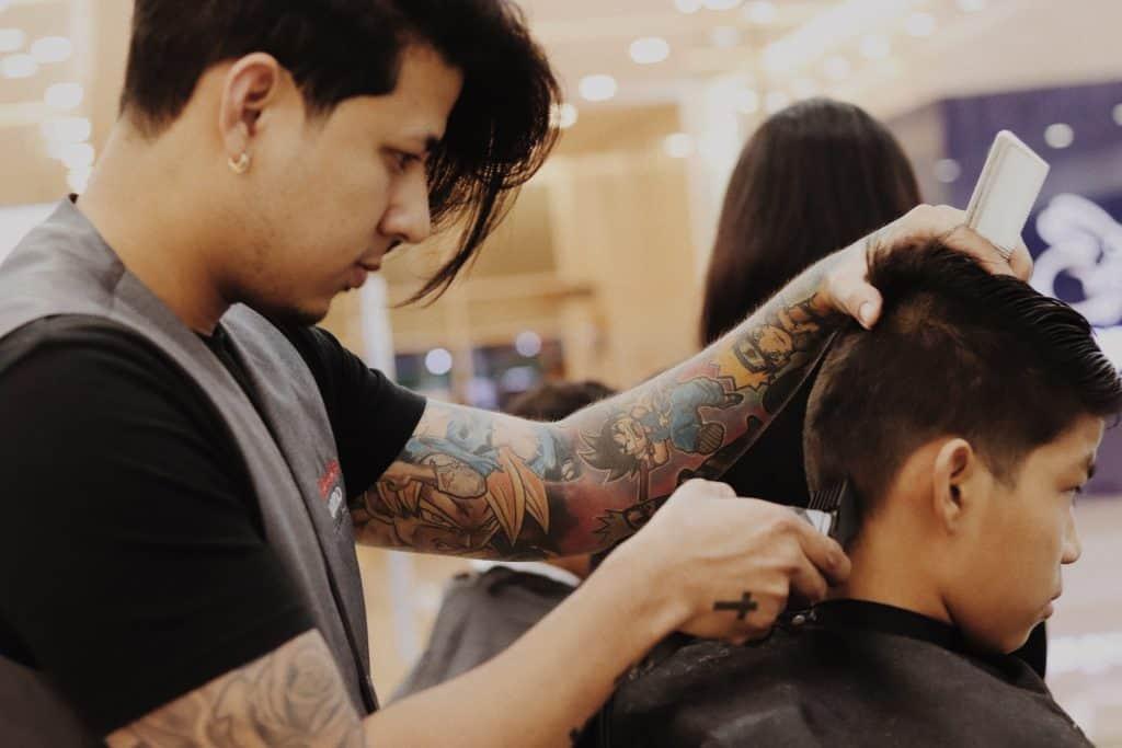 Imagem de homem cortando o cabelo de um garoto.