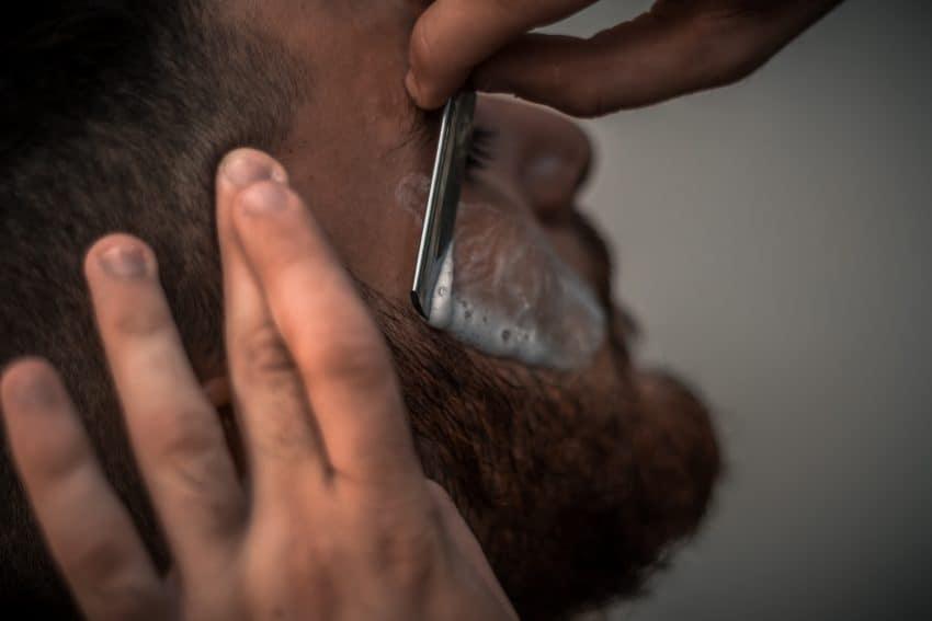 Imagem mostra duas mãos barbeando um homem. A mão esquerda delimita o espaço, enquanto a direita passa a lâmina sobre uma pequena área do rosto do homem com espuma.
