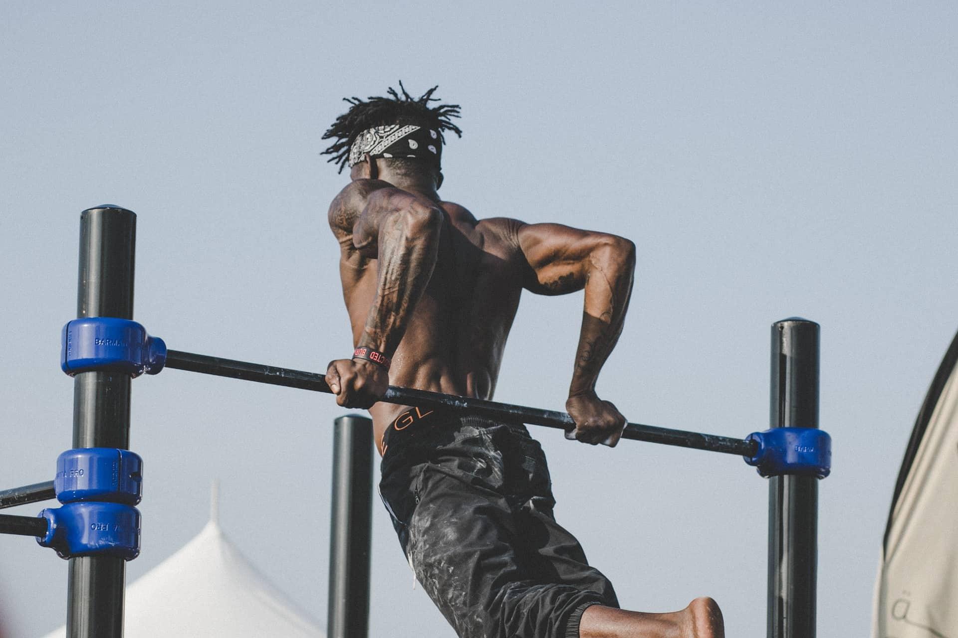 Homem musculoso e sem camisa de costas levando seu corpo com as mãos em uma barra.