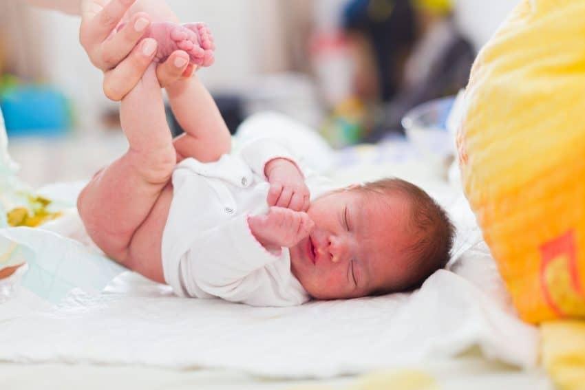 Mãe trocando filho recém-nascido na cama.